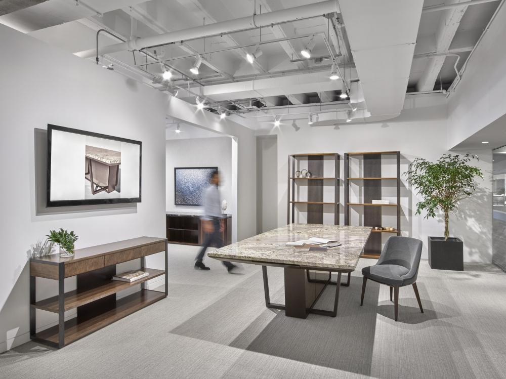 Preview of Crossbeam | Conference Table | COM Stone Top | Aged Bronze Base | Bronze Mirrored Acrylic Panels | Person Walking | Chicago Showroom