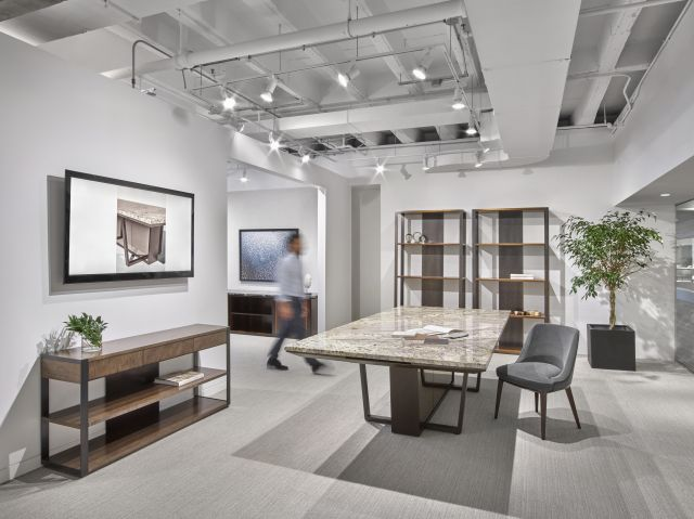 Crossbeam | Conference Table | COM Stone Top | Aged Bronze Base | Bronze Mirrored Acrylic Panels | Person Walking | Chicago Showroom