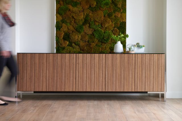 Flow Credenza | Canyon Paldao Veneer | Black Satin Glass Top | Polished Chrome Cradle Base | Person Walking